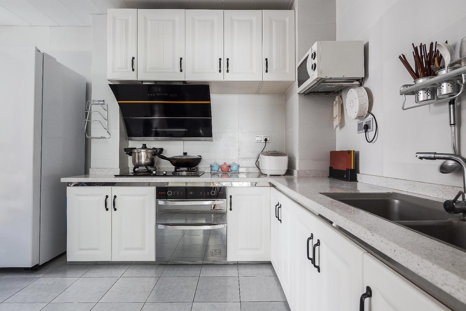 厨房地面通铺灰色瓷砖,立面浅色瓷砖搭配白色橱柜,灰色麻点台面耐脏易